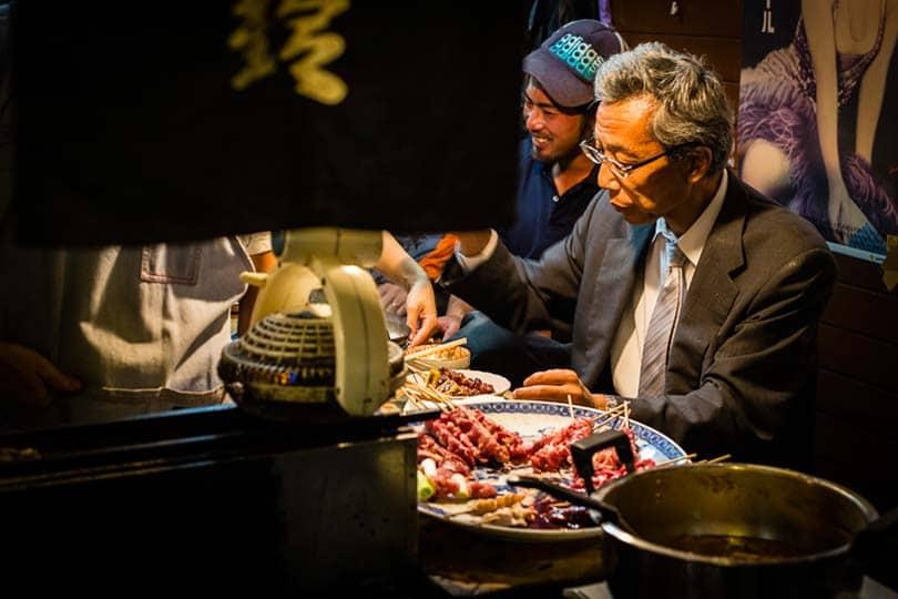 Depois de um dia de trabalho, um empregado de uma multinacional delicia-se com espetadas yakitori numa tasca em Shinjuku.