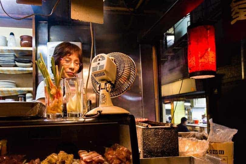 Numa das várias tascas que povoam os becos de Shinjuku, uma senhora prepara uma refeição de espetadas yakitori