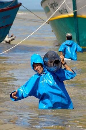 Velho pescador carrega um atum para terra firme, em Itaipava