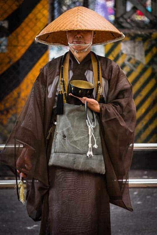 Um monge budista espera pacientemente por esmolas à saída da estação de Ueno