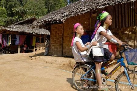 Jovens Karen de bicicleta na rua principal da aldeia