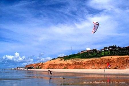 Praticantes de kitesurf em ação na praia de Canoa Quebrada, Brasil