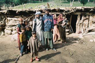 Família de pastores em frente à sua casa em Caxemira