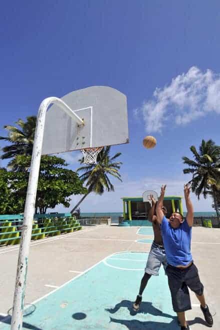 Jogo de basquetebol no campo com a melhor localização do planeta: as palmeiras marcam o início do areal