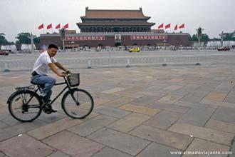 Um ciclista atravessa a praça Tiananmen, em frente à porta principal da Cidade Proibida