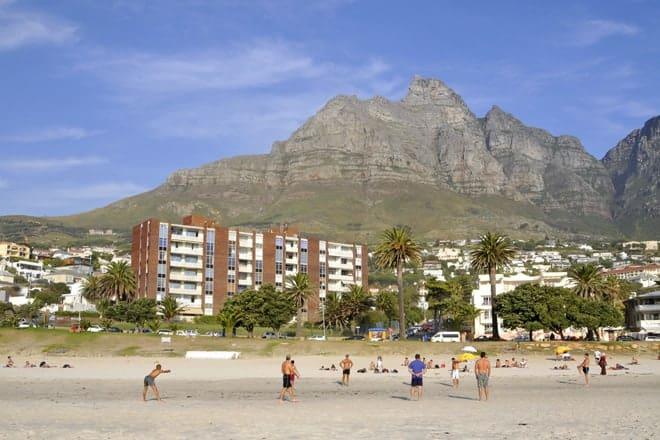 Beach blak í Camps Bay með hluta af tólf postula fjöllum í bakgrunni