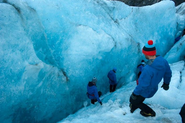 Grupo de turistas explorando o Franz Josef
