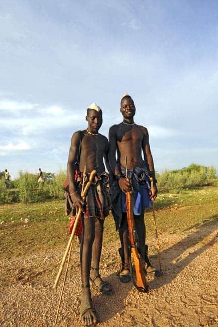 Dois jovens Himba posando para a foto com as armas em punho