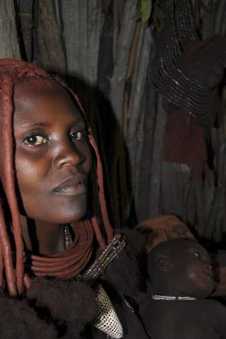 Retrato de uma bela mulher Himba no interior da sua modesta cubata de madeira, no mato, entre Opuwo e as cataratas de Epupa