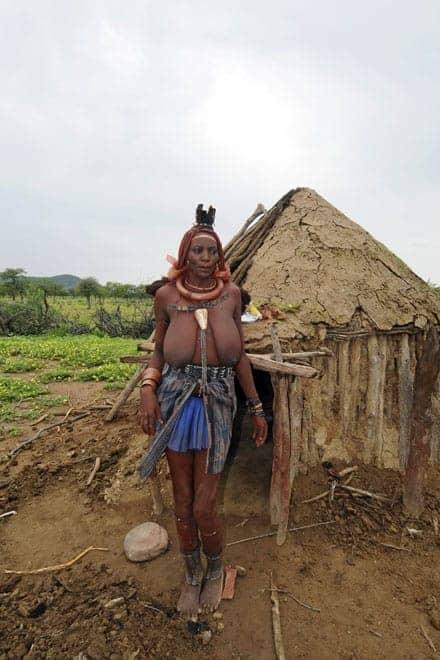 Matriarch van de Himba-familie bij de deur van zijn hut