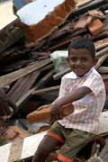 Uma criança ajuda o seu pai a recolher tijolos intactos por entre os escombros da sua casa, Galle, Sri Lanka