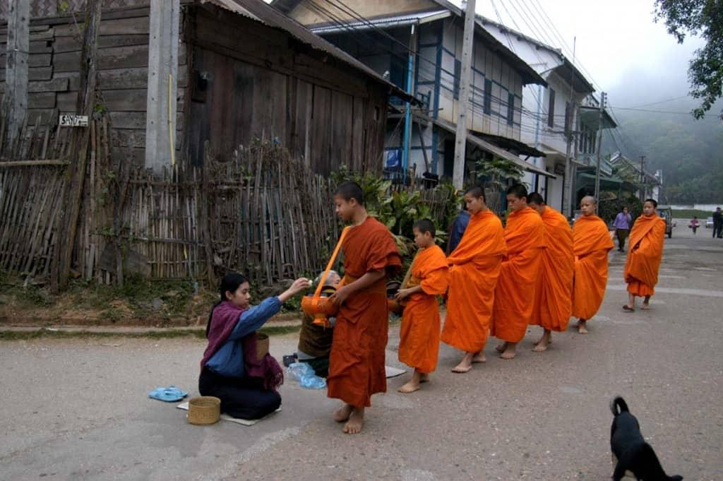 Monges budistas recolhendo as oferendas em Luang Prabang, Laos