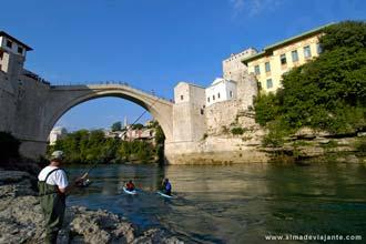 Um homem pesca junto à stari most de Mostar, Bósnia-Herzegovina