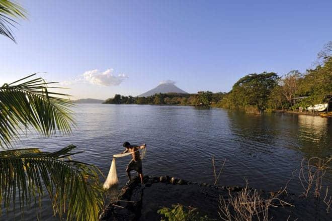 Ao fim da tarde, com o vulcão Concepción ao fundo, um jovem pescador lança a rede no lago Cocibolca