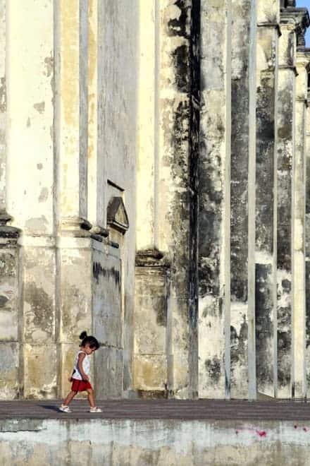 Uma criança passa defronte da Catedral de León, Nicarágua