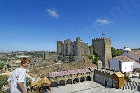 Turista passeando nas muralhas de povoação, com o Castelo de Óbidos ao fundo