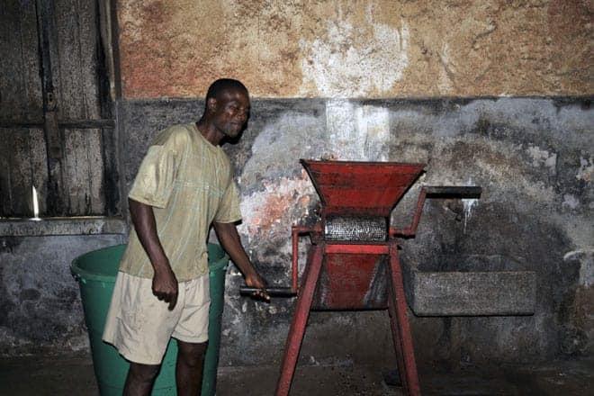 Miguel demonstra o funcionamento de uma máquina utilizada no processamento do cacau, São Tomé