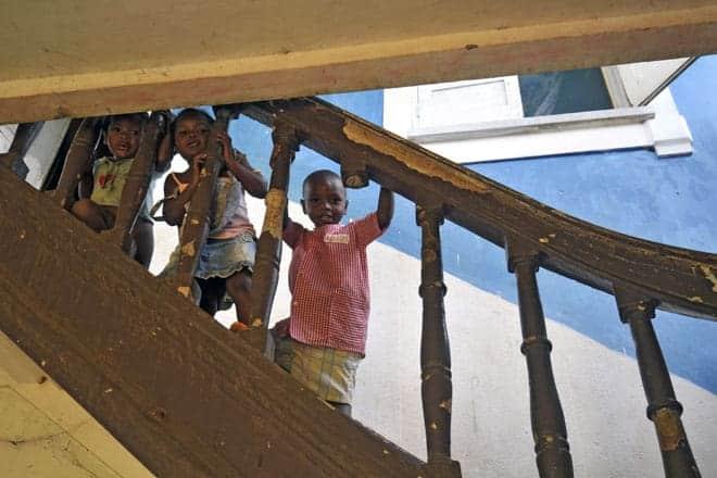 Miúdos espreitam o visitante na escadaria do antigo hospital da roça Água Izé