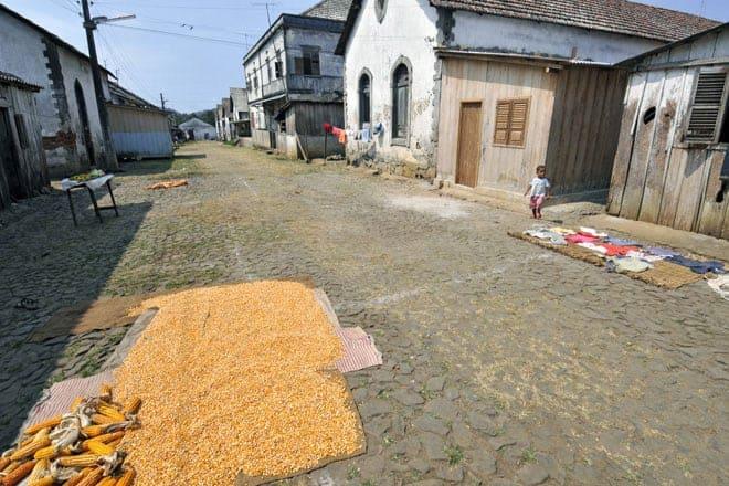 Secando milho e roupa no empedrado de uma ruela